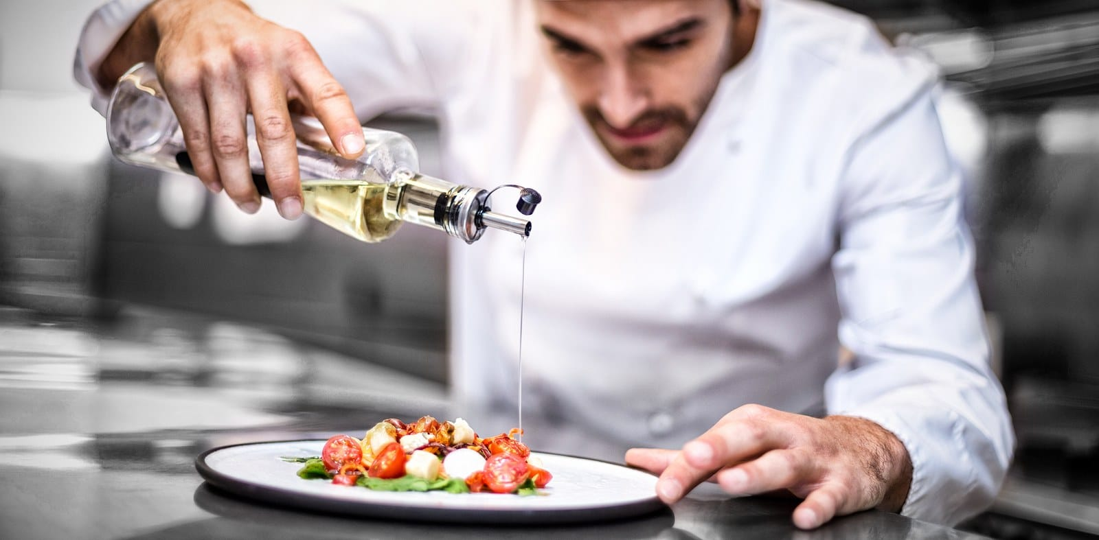 A chef carefully pouring oil on a salad