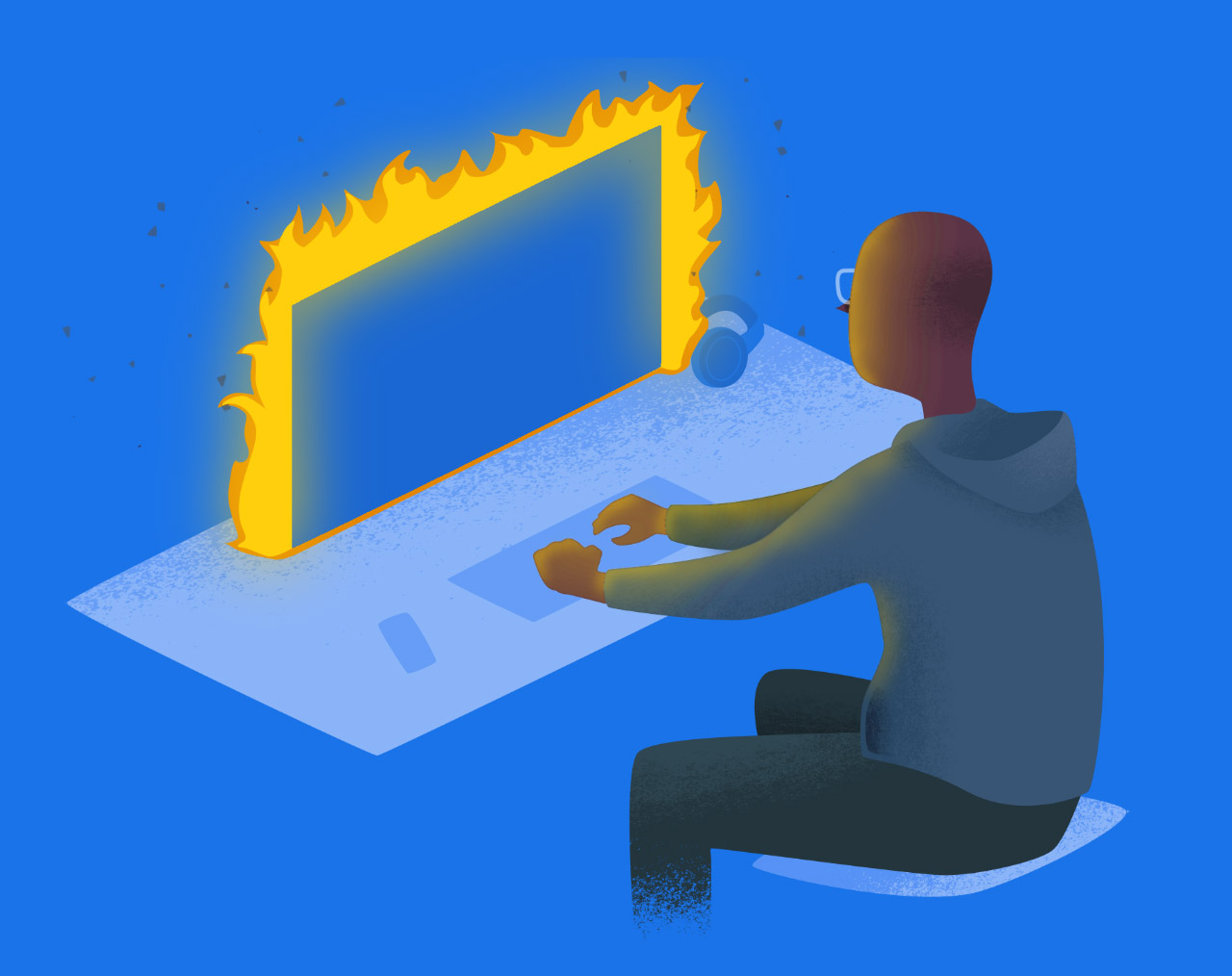 A developer sitting at a computer that's on fire